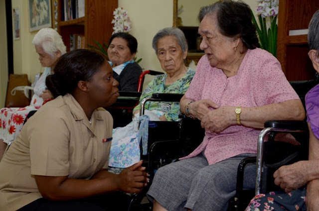 A nurse kneels next to an older woman sitting in a wheelchair