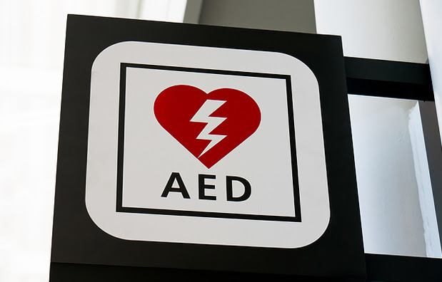 A sign with a heart and thunderbolt that says AED, which means Automated External Defibrillator.