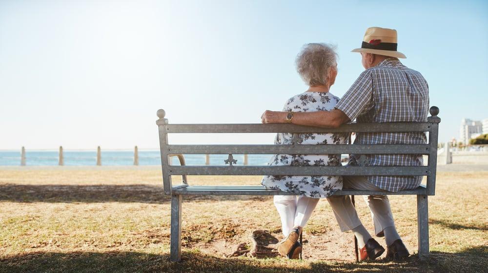 Senior couple sitting on a bench on the beach