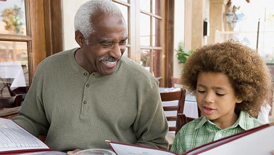 Grandfather and grandson reading a menu