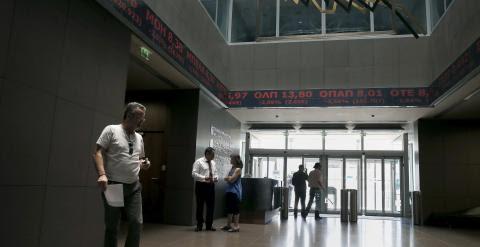 Un hombre camina por la Bolsa de Atenas, cuyos paneles muestran los indicadores del mercado en rojo. REUTERS/Alkis Konstantinidis