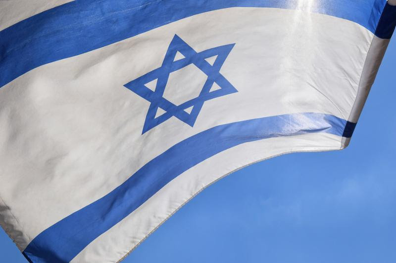 Star of David on a blue and white israeli flag against a bright sky