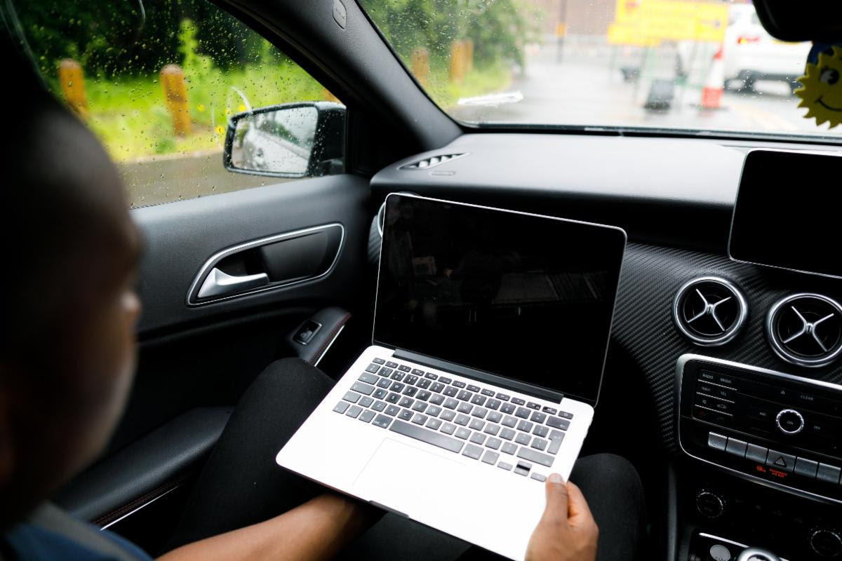 Photo of person on computer in car, by Humphrey Muleba on Unsplash