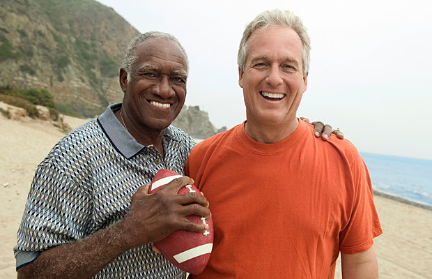 Two men on the beach holding a football.
