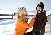 A mother applying sunscreen to her son during winter.