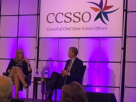 Frank Brogan talks with CCSSO Executive Director Carissa Miller on a stage underneath a large sign that reads CCSSO Council of Chief State School Officers.