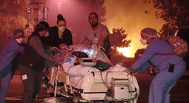Doctors and nurses evacuating patient in bed from hospital with fire in background