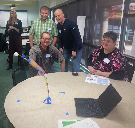 A group of teachers sit around a table observing an experiment with a marshmallow on pencils taped together.