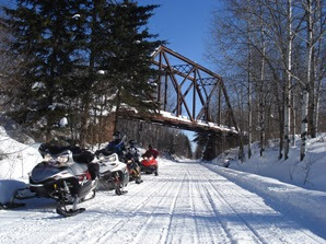 Three snowmobiles sit on the side of a snow-covered trail under a bridge.
