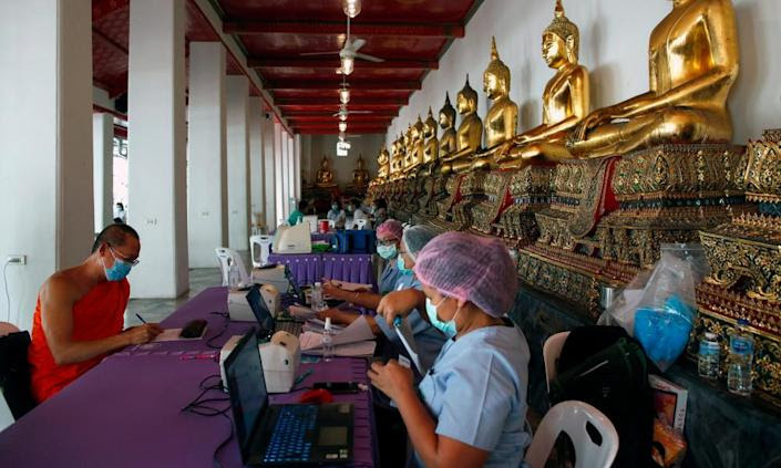 "<span class=""element-image__caption"">A Thai Buddhist monk registers for a Covid-19 swab test at Wat Pho temple in Bangkok in May.</span> <span class=""element-image__credit"">Photograph: Rungroj Yongrit/EPA</span>"