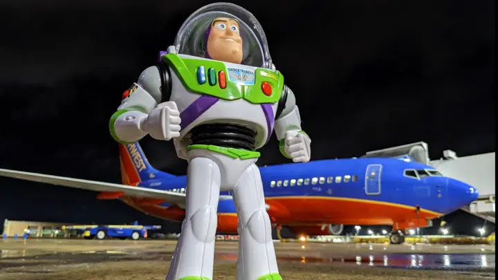 Buzz outside with a Southwest plane behind him