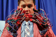 Brendon Villalobos demonstrates gloves he made that translate hand gestures into computer text input with the help of Intel's latest sensor-laden chip package, Curie.