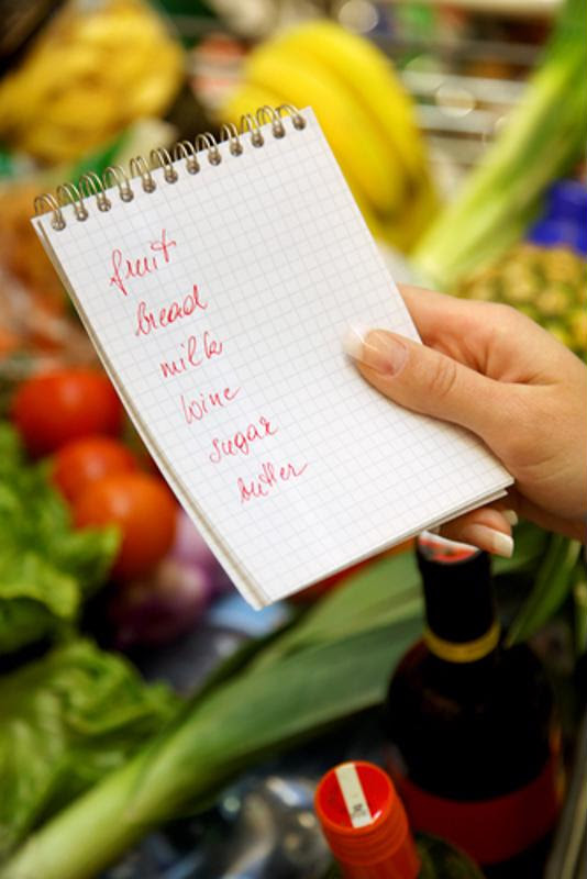 A woman's hand holding a grocery list with produce in the background.