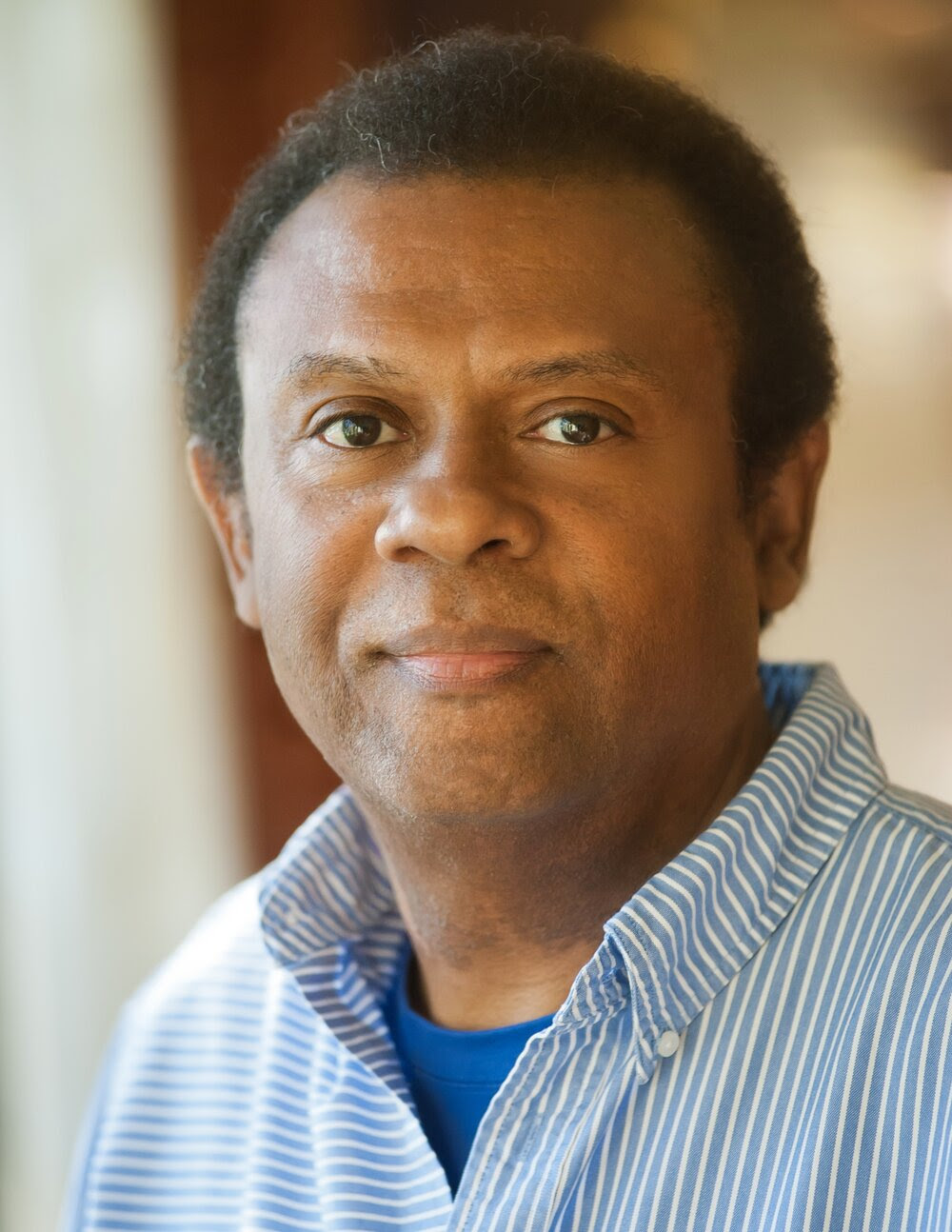 Headshot of Dr. Nicky Sheats, Black male wearing a blue shirt and blue and white striped collared shirt. Blurred tan and brown background.