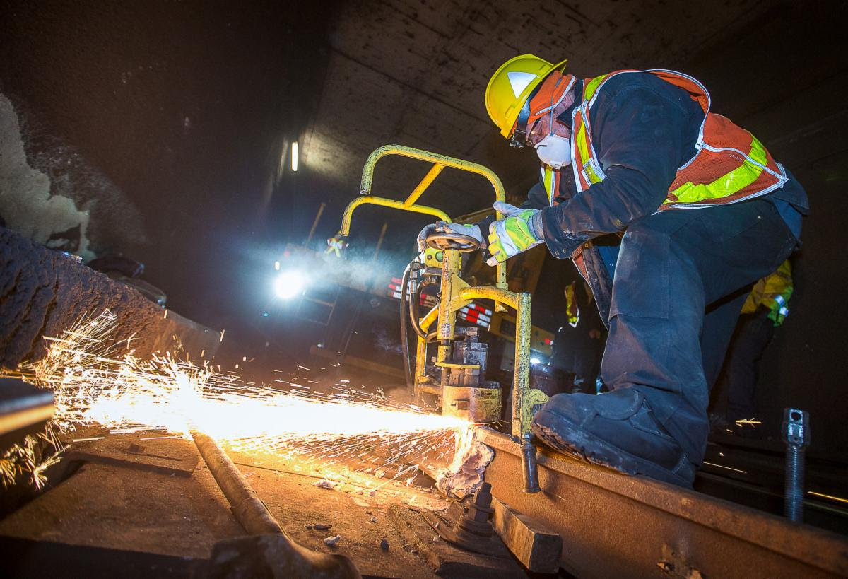 Sparks shoot out as a TTC employee works on a subway track replacement