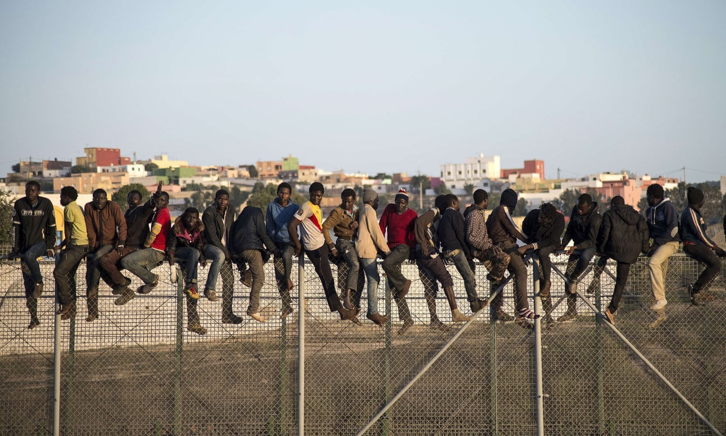 Would-be immigrants on a fence separating Morocco from the north African Spanish enclave of Melilla.