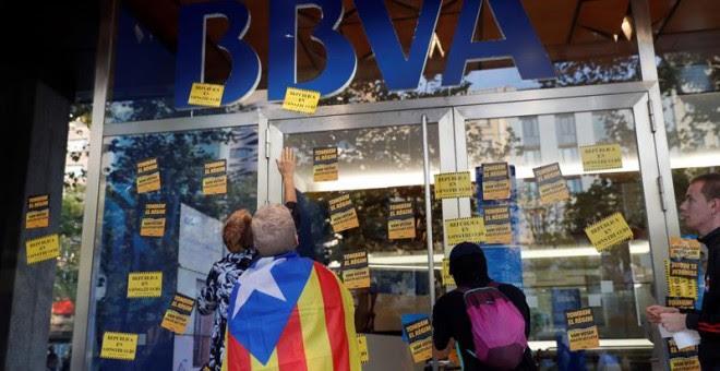 Manifestantes colocando pegatinas en una sucursal del BBVA. - EFE