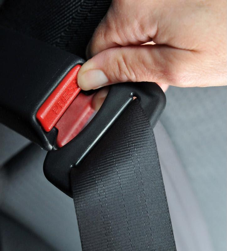 A driver fastens a seat belt.