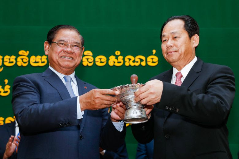 Chea Sophara (right) receives an official stamp from Sar Kheng during his appointment ceremony to Minister of Land Management.