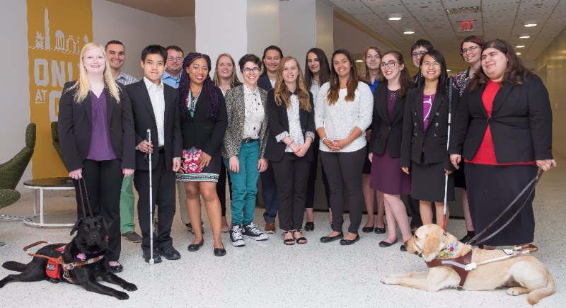 The AAPD Summer Internship Program Class of 2017 poses for a photograph. There are 17 smiling individuals with various disabilities and two guide dogs present.