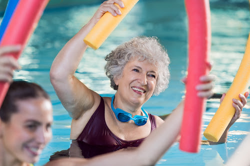 Smiling senior woman doing aqua fitness with swim noodles. Happy mature healthy woman taking fitness classes in aqua aerobics. Healthy old woman holding swim noodles doing aqua gym with young trainer.