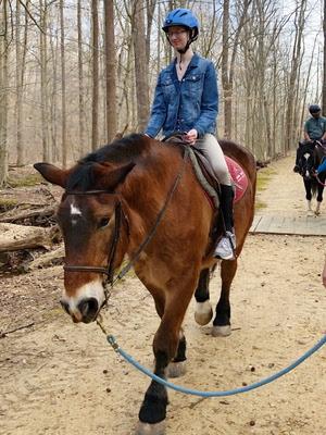 Delaney rides Yogi on the trail