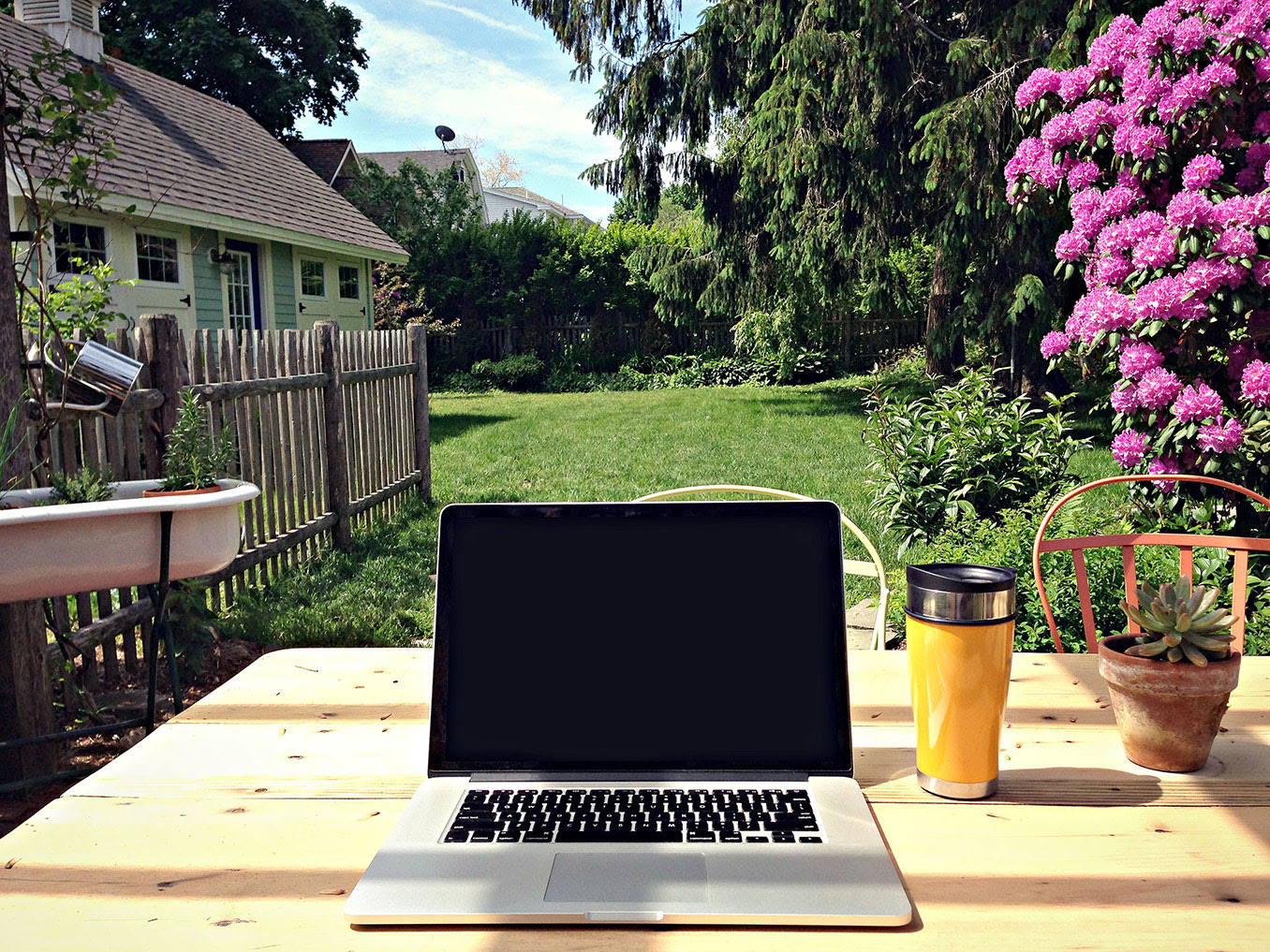 A laptop at a desk, set in a beautiful outdoor garden