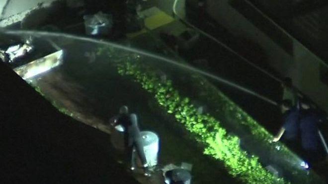Pessoa jogando água em papéis que queimavam em consulado chinês em Houston
