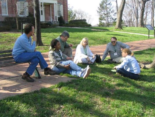 A group of people sitting on the ground having a discussion