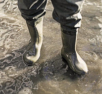 Person with heavy boots standing in floodwaters