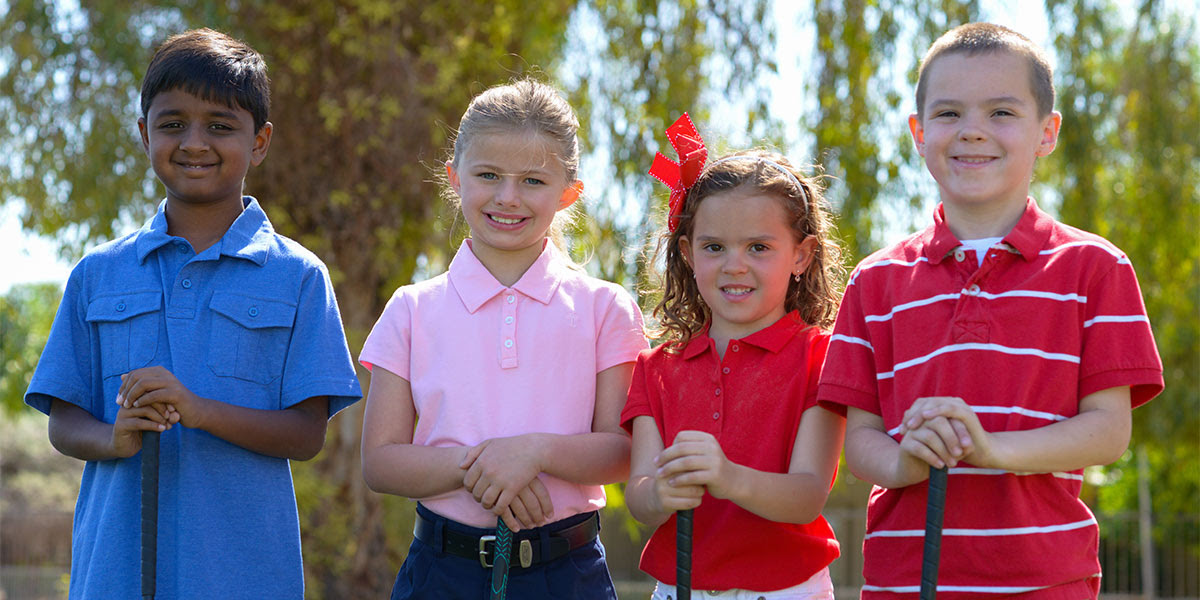 4 children standing with golf clubs