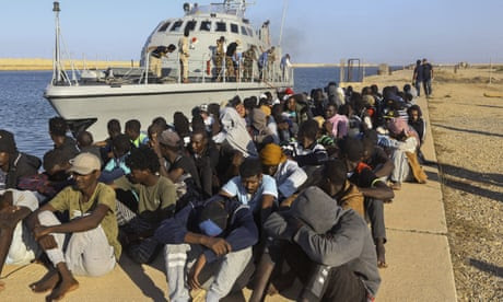 Rescued refugees seated next to a coastguard boat in Khoms, Libya, 1 October 2019