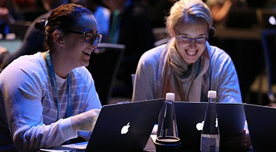 Two people smiling while working together on laptops