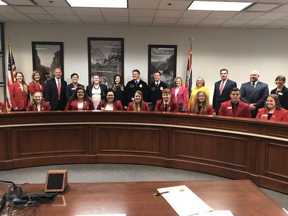 The Governor and the State Superintendent are surrounded by high school students who serve as state officers for Career Technical Student Organizations and their state advisors in a legislative committee meeting room.
