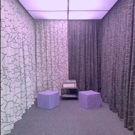 Photograph of the inside of an elevator with gray carpet, white and charcoal colored curtains, two purple cubes for people to sit on, and a record player.